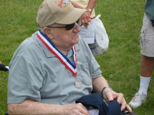 WWII B-25 pilot Larry Kiger with his hat and medalion from the Yankee Air Museum crew