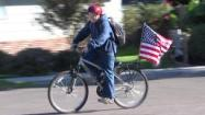 Cody Alicea rides bike with a US flag
